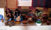 Moroccan women showing traditional method of pressing argan oil in co-op