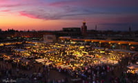 Food stalls in Jemaa el Fna Square at dusk in Marrakech Morocco former imperial city Koutoubia mosque in background